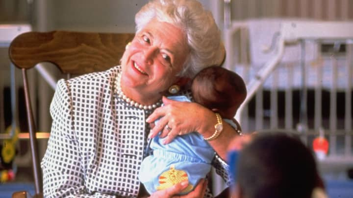First Lady Barbara Bush holding baby while two-year-old child takes photo with a toy camera at hospice for children with AIDS.