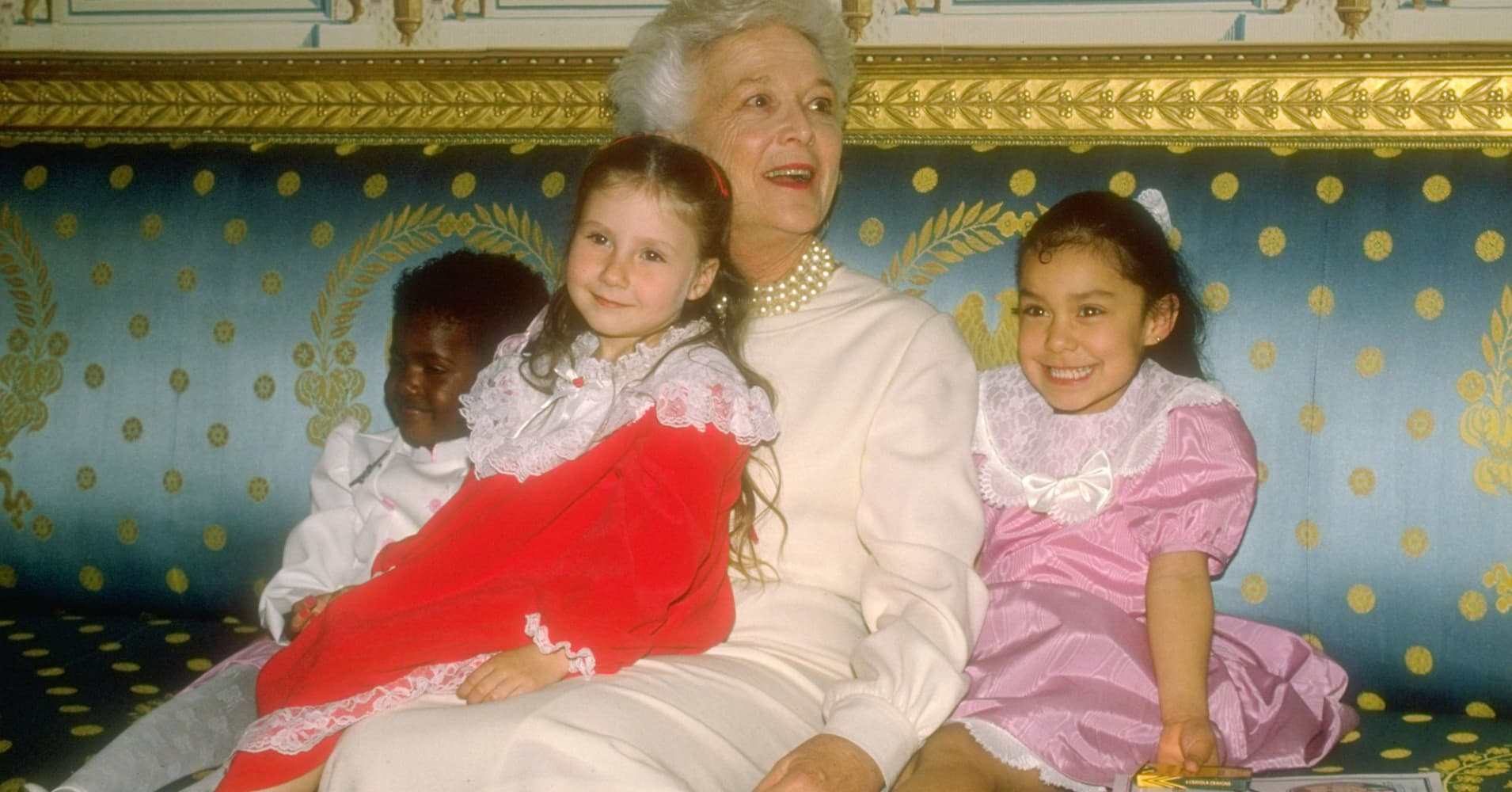 First Lady Barbara Bush, sporting her signature pearls, cuddling with a trio of little girls at fete for the Barbara Bush Foundation for Family Literacy in 1989.