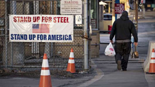 A man walks past a 'Stand Up For Steel, Stand Up For America' sign while arriving at the United States Steel Corp. Clairton Plant coke manufacturing facility as emissions rise in Clairton, Pennsylvania.