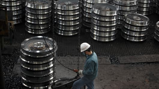 A worker stands among stacks of train carriage wheels at a plant in Maanshan, near Nanjing, China.