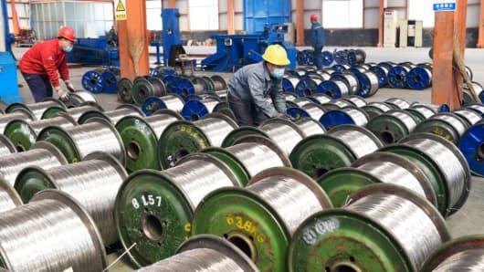 Workers move rolls of aluminium at a factory in Zouping in China's eastern Shandong province on April 7, 2018.