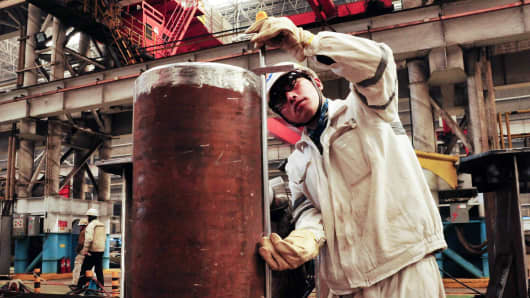 A Chinese worker measures a pipeline at an offshore oil drilling platform in Qingdao, east China's Shandong province.