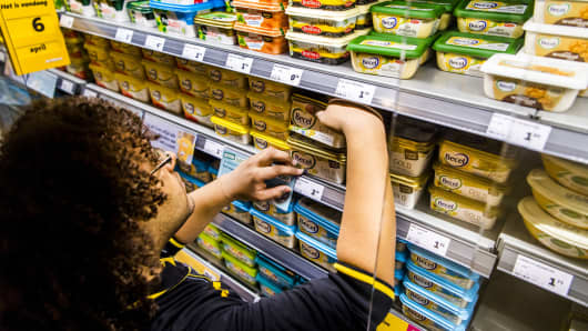An employee arranges Unilever's margarine brands Becel, Blue Band, Bona and Zeeuws Meisje in a supermarket.