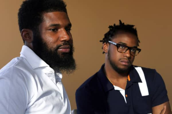 In this Wednesday, April 18, 2018 photo, Rashon Nelson, left, and Donte Robinson, right, listen to a reporter's question during an interview with The Associated Press in Philadelphia.