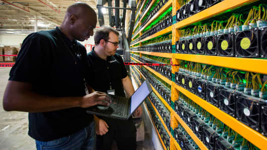 Two technicians look at bitcoin mining at Bitfarms in Saint Hyacinthe, Quebec on March 19, 2018.