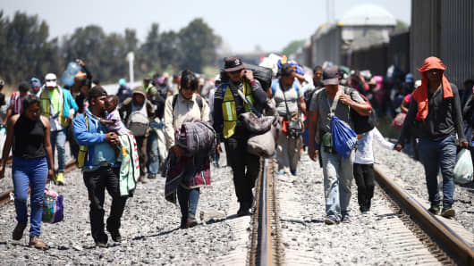 Central American migrants, moving in a caravan through Mexico, disembark from a freight train as they walk on a railway track after stopping the train on a rail line, in Irapuato, Guanajuato state, Mexico April 15, 2018.