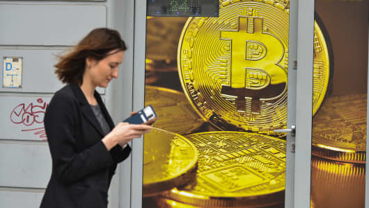 A woman passes in front of a Bitcoin exchange shop.