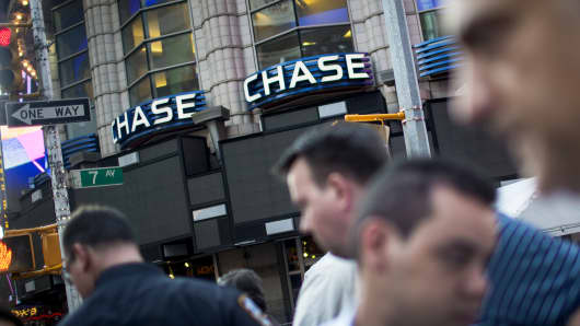 Pedestrians pass in front of a JPMorgan Chase & Co. bank branch in New York.