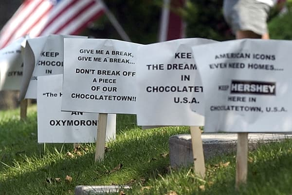 Yard signs protesting the proposed sale of Hershey Foods are lined along Caracas street in Hershey, Pennsylvania, September 3, 2002.