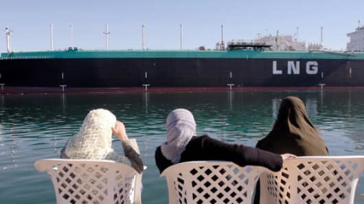 Women observe the Tenaga Satu, a Liquefied Natural Gas (LNG) tanker owned by MISC Berhad, a Malaysian shipping company, as it sails northbound on the Suez Canal in Ismailia, Egypt