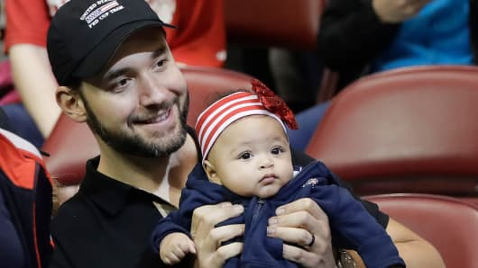 Alexis Ohanian, husband of USA's Serena Williams, holds their baby, Alexis Olympia Ohanian Jr., before the doubles match in the first round of Fed Cup tennis competition in Asheville, N.C., Feb. 11, 2018.