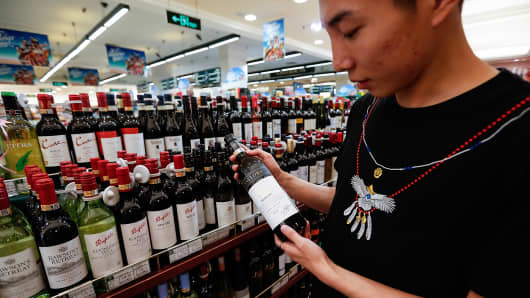 A customer looks at a bottle of wine at a supermarket in Beijing, China.