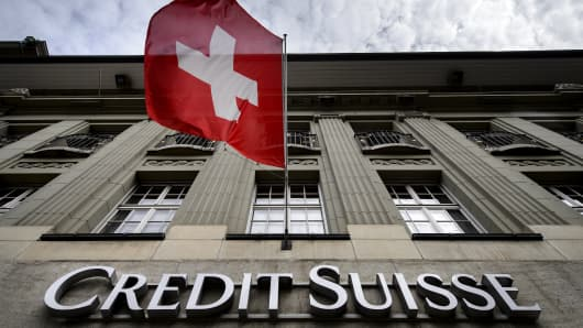 A Swiss flag flies over a sign of Swiss bank Credit Suisse on May 8, 2014 in Bern.
