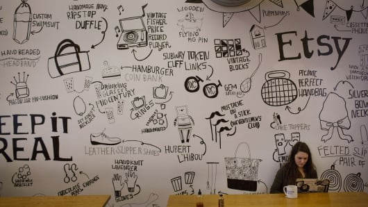 An employee works while sitting under a mural at Etsy Inc. headquarters in Brooklyn.