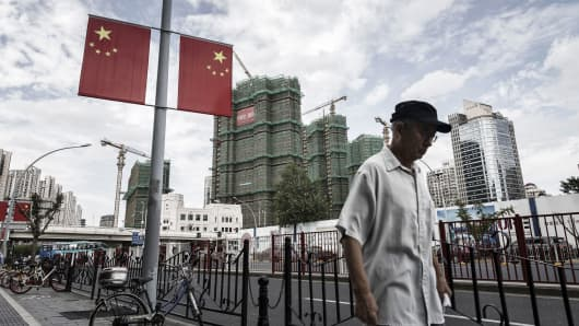 A pedestrian walks past Chinese national flags hanging on a street light as residential buildings stand under construction in the background in Shanghai, China.