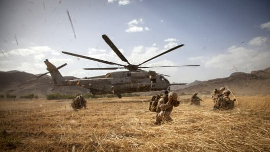 A Sikorsky helicopter lands near Marines with Fox Company, 2nd Battalion, 8th Marines, Regimental Combat Team 7, and Afghan National Security Forces provide security during Operation Nightmare in Nowzad, Afghanistan, June 6, 2013.
