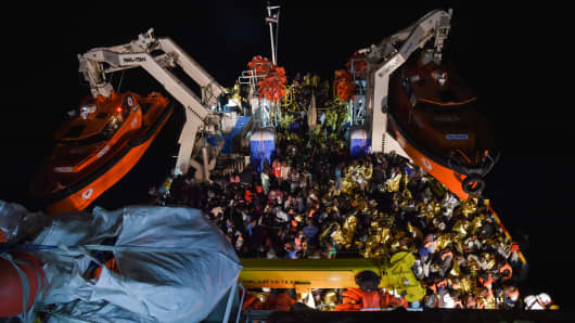 Migrants and refugees are transferred from the Topaz Responder ship run by Maltese NGO 'Moas' and the Italian Red Cross to the Spanish war ship Navarra, after being rescued off the coast of Libya on November 5, 2016.