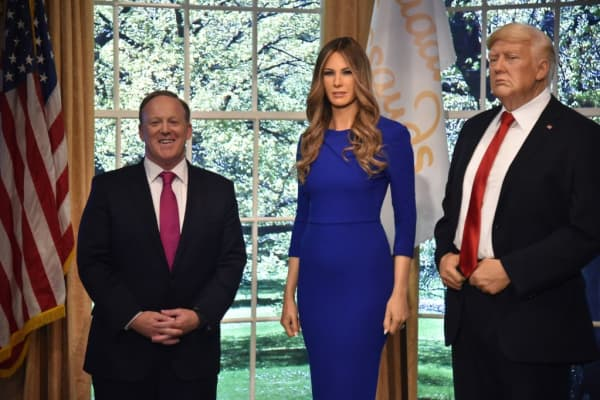Former White House press secretary Sean Spicer stands next to waxworks of First Lady Melania Trump as well as the President at Madame Tussauds New York City in April 2018