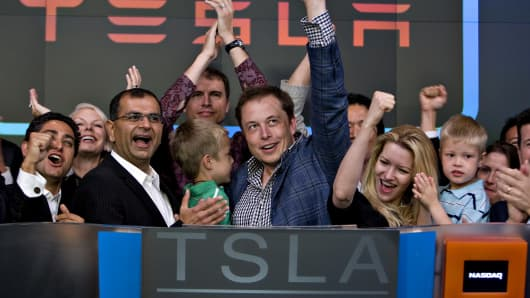 Elon Musk, chairman and chief executive officer of Tesla Motors, center, participates in the opening bell ceremony at the Nasdaq Marketsite with his twin boys Griffin, green shirt at center, and Xavier, right in blue shirt, and his fiancee (at the time) Talulah Riley, second from right, in New York, U.S., on Tuesday, June 29, 2010.