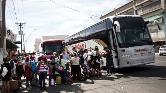 Migrants in a caravan of Central American asylum-seekers board buses in Mexicali, Mexico, Thursday, April 26, 2018, for a two-hour drive to Tijuana to join up with about 175 others who already arrived.