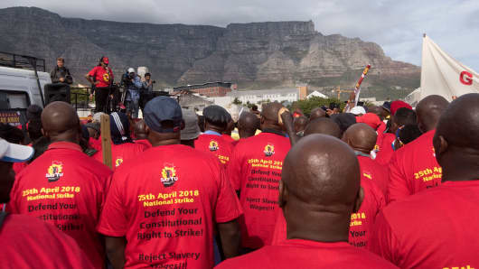Members and supporters of the South African Federation of Trade Unions protest in Cape Town on April 25, 2018, with Table Mountain seen in the background.