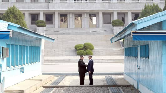 North Korean leader Kim Jong Un (L) takes hand of South Korean President Moon Jae-in (R) to cross the military demarcation line (MDL) to the north side upon meeting for the Inter-Korean Summit April 27, 2018 in Panmunjom, South Korea.
