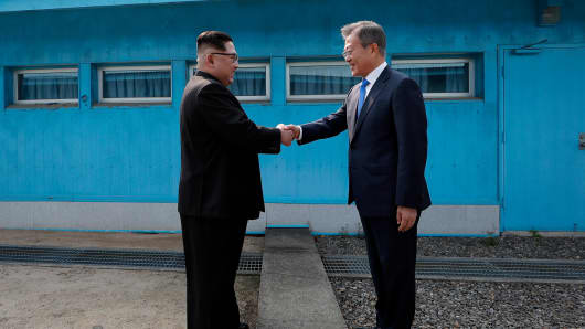 North Korean Leader Kim Jong Un (L) and South Korean President Moon Jae-in (R) shake hands over the military demarcation line upon meeting for the Inter-Korean Summit on April 27, 2018 in Panmunjom, South Korea.