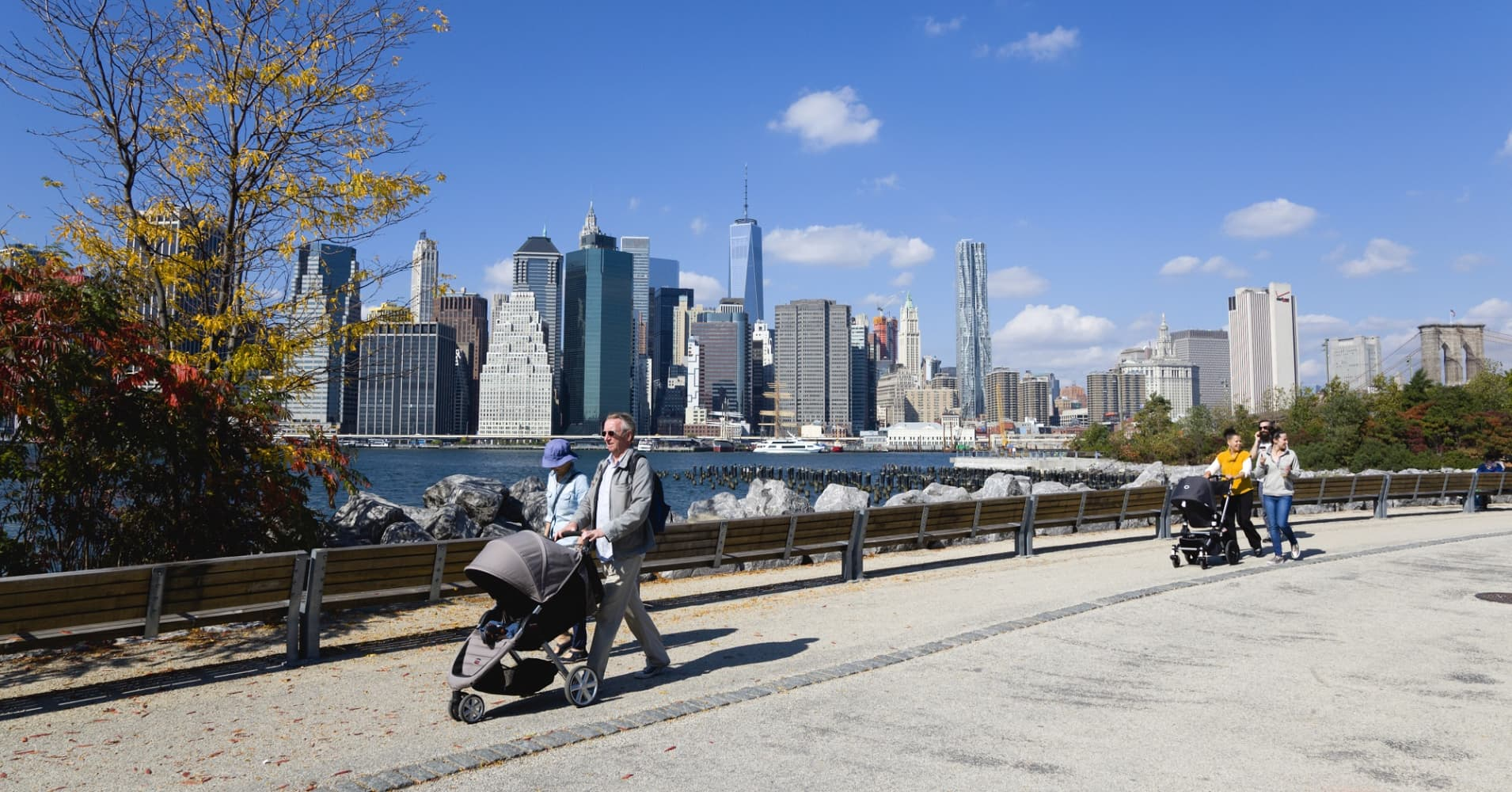 USA, New York, Brooklyn Bridge Park, couple in autumn pushing prams along a path between Pier 1 and Pier 2 with the Lower Manhattan skyscraper skyline and the East River beyond.