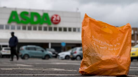 In this arranged photo illustration, a Sainsbury's shopping bag is seen on the ground in the car park of an Asda supermarket on April 29, 2018 in London, England. Major supermarket chains Sainsbury's and Asda have been reported to be in talks over a £10 billion merger deal which would mean the possible new supermarket group would have 31.4% market share, compared with Tesco's 25.6%.