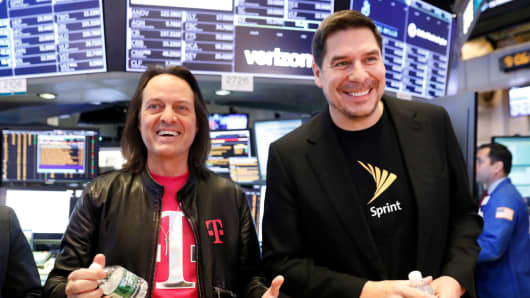 T-Mobile CEO John Legere (L) and Sprint CEO Marcelo Claure pose for pictures on the floor of the New York Stock Exchange April 30, 2018.