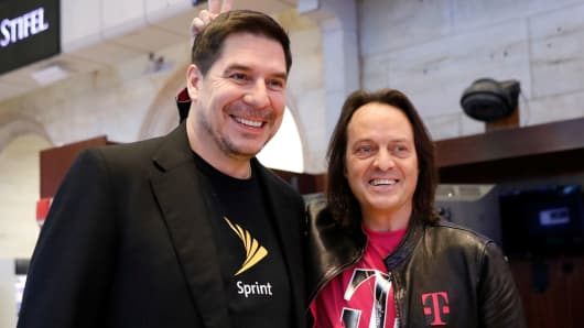 T-Mobile CEO John Legere (R) and Sprint CEO Marcelo Claure pose for pictures on the floor of the New York Stock Exchange, April 30, 2018.