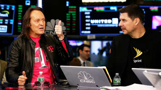T-Mobile CEO John Legere (L) speaks as Sprint CEO Marcelo Claure looks on at the New York Stock Exchange, April 30, 2018.