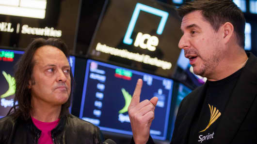 John Legere, chief executive officer and president of T-Mobile US Inc., left, listens as Marcelo Claure, chief executive officer of Sprint Corp., speaks during an interview on the floor of the New York Stock Exchange (NYSE) in New York, U.S., on Monday, April 30, 2018.