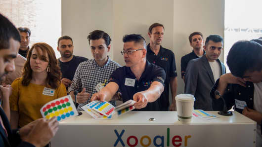 Xoogler Demo Day organizer Kevin Yen hands out stickers to participants: Green for startups, blue for investors, and red for press.