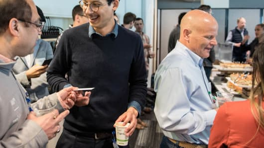 During one of the mingling sessions, for which Google provided sandwiches and cookies, participants swap business cards.