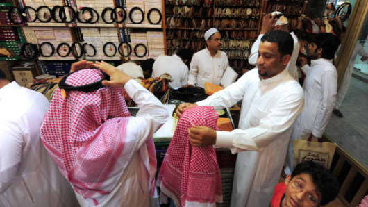 Saudi men shop with their children at a mall in Jeddah late on September 17, 2009 ahead of celebrations for Eid al-Fitr.