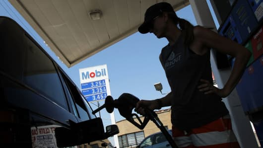 A woman fuels her SUV at an Exxon Mobile gas station in Chicago.