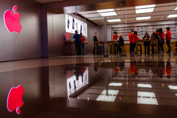 An Apple flagship store lights up the red logo.
