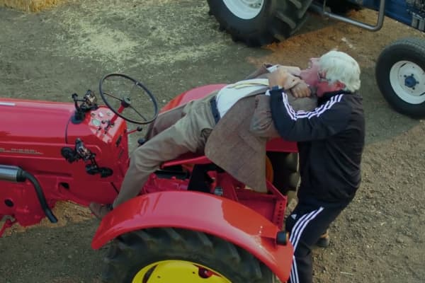 Jay Leno puts Jeff Foxworthy in a headlock while he's riding the 1958 Porsche Tractor