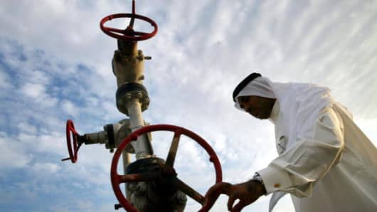 Khalid Abdulla Alhajeri looks at a natural gas pipe November 3, 2002 in Manama, Bahrain.