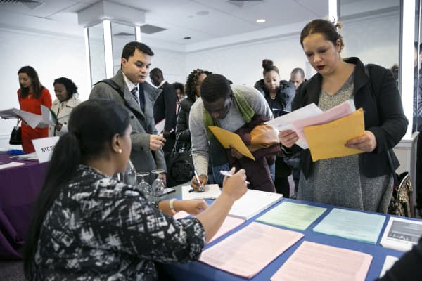 A New York Department of City Administrative Services representative, left, speaks with job seekers during a Catalyst Career Group job fair in New York.