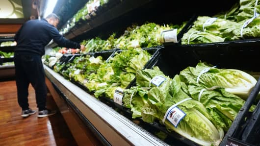 A man shops for vegetables beside Romaine lettuce stocked and for sale at a supermarket in Los Angeles.