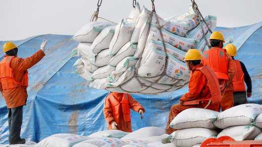 Workers transport imported soybean products at a port in Nantong, China.