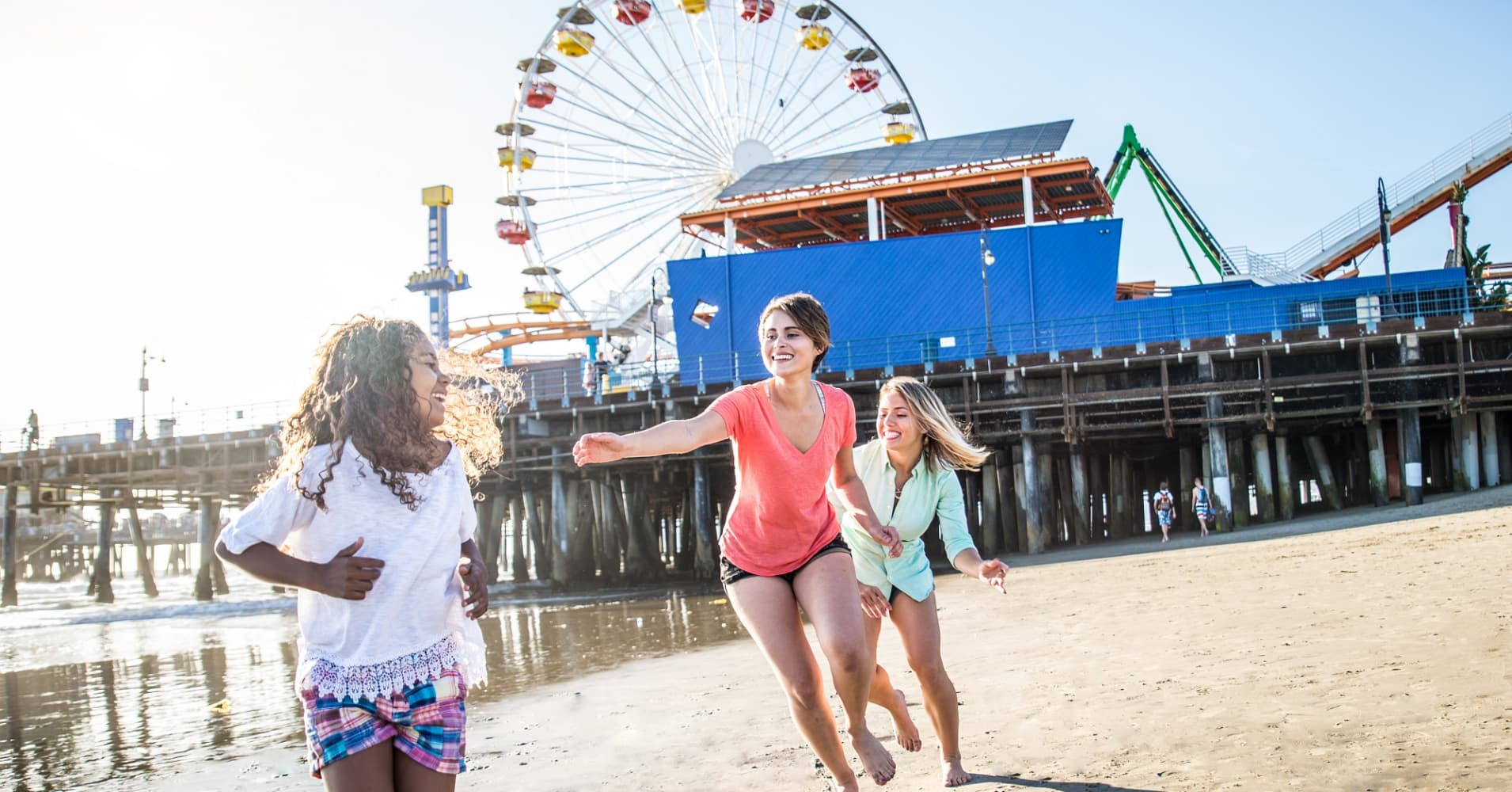 Two mothers and their daughter play by the Santa Monica Pier in California.