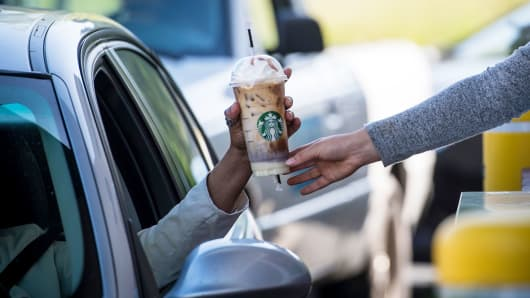 An employee passes a drink order to a customer at the drive-thru of a Starbucks coffee shop in Rodeo, California.