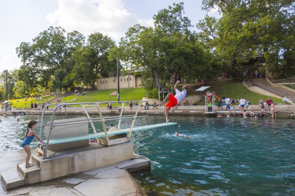 Swimmers on a hot day in Barton Springs Pool. Barton Springs Pool is a man-made recreational swimming pool located on the grounds of Zilker Park in Austin, Texas.