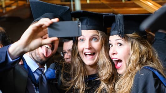 Three university students posing for a selfie on graduation day.