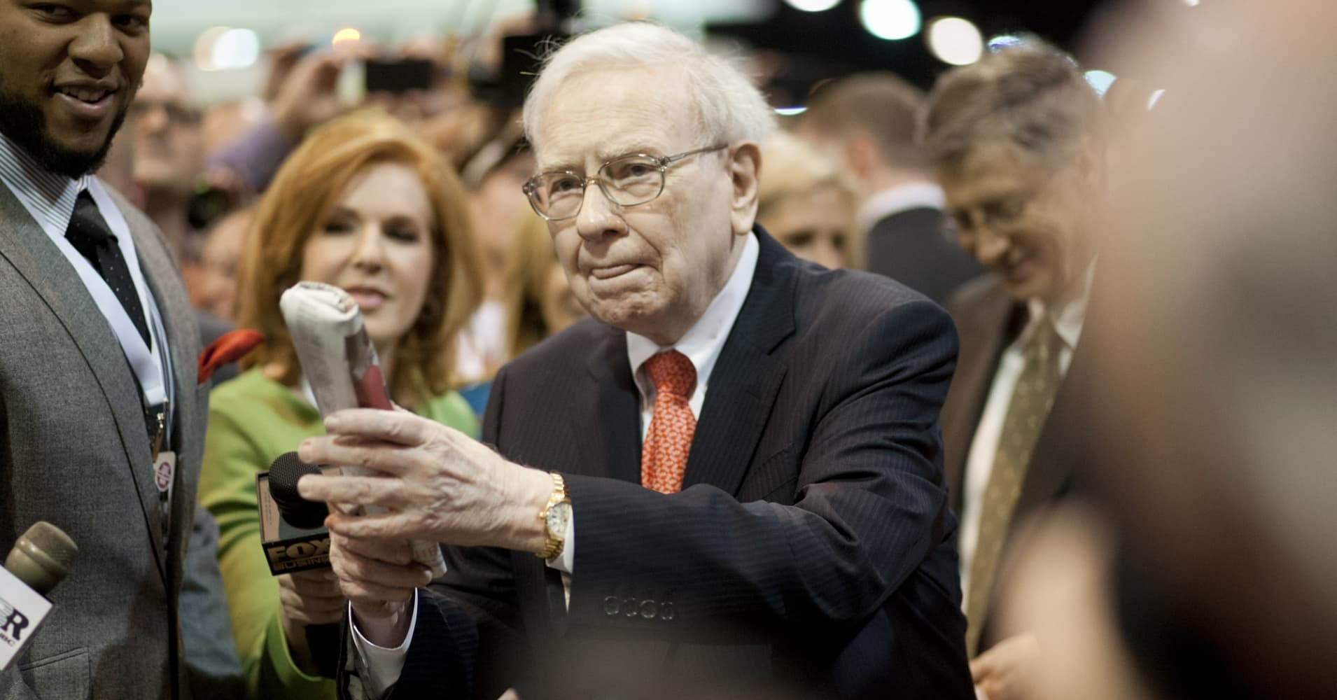 Warren Buffett, chairman and chief executive officer of Berkshire Hathaway Inc., prepares to throw a newspaper as he tours the exhibition floor prior to the start of the Berkshire shareholders meeting in Omaha, Nebraska, U.S., on Saturday, May 4, 2013.