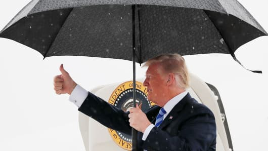 President Donald Trump gives a thumbs up while holding an umbrella in the rain as he arrives at Dallas Love Field aboard Air Force One to address the National Rifle Association Convention in Dallas, Texas U.S., May 4, 2018.