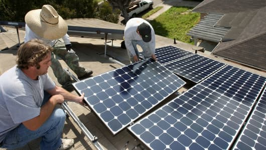 Employees of Solar Forward install solar electric panels on a residential rooftop in Santa Monica, California.